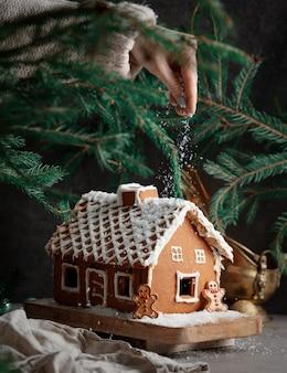 Hand giet een sneeuw op kerst peperkoek huis versierd met room