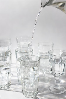 Hand giet vers water uit een karaf in een glas