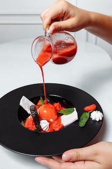 Hand gieten aardbeiensaus aan ijs met verse aardbeien en versierd met munt. een zeer populair zomerdessert