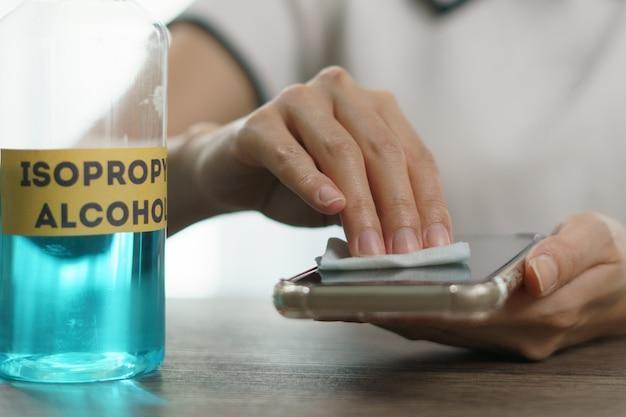Hand gieten ethylalcohol uit fles in een katoenen stuk voor schone mobiele telefoon