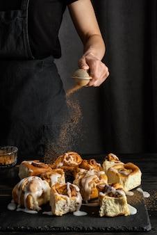 Hand gieten kaneel op dessert close-up Gratis Foto