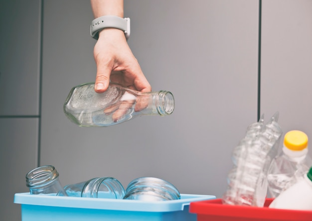 Hand gooien van de glazen fles naar de container voor het sorteren van afval