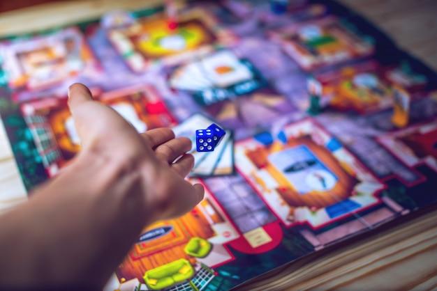 Hand gooit de dobbelstenen op het bordspel