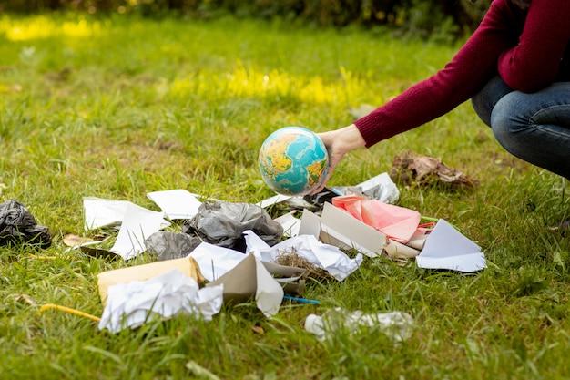 Hand gooit een wereldbol in het afval.