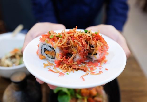 Hand greep gerecht van gerolde sushi in de keuken