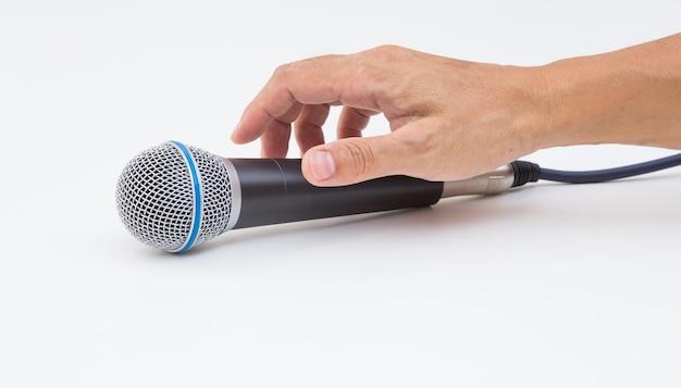Hand grijpende microfoon op wit