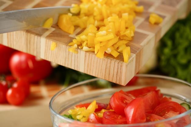 Hand groenten toevoegen aan glazen kom