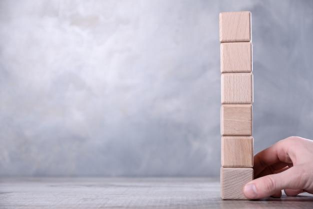 Hand haalt lege houten kubus met ruimte voor uw woord, brief, symbool op de tafel. de invloed van één persoon op het team. plaats voor tekst, gratis exemplaarruimte