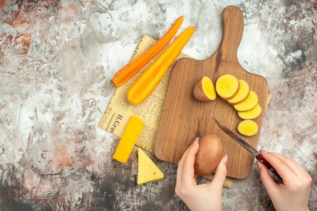 Hand hakken van verschillende groenten en twee soorten kaasmes op houten snijplank op een oude krant op gemengde kleur achtergrond