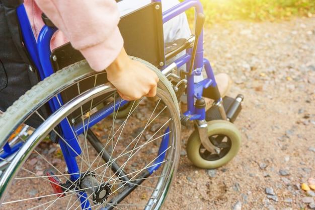 Hand handicap vrouw in rolstoel wiel op weg in ziekenhuis park