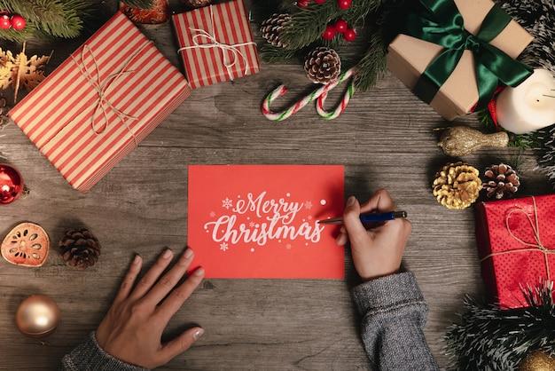Hand het schrijven vrolijke kerstmis tekst van de groetkaart met kerstmisdecoratie op houten lijst.