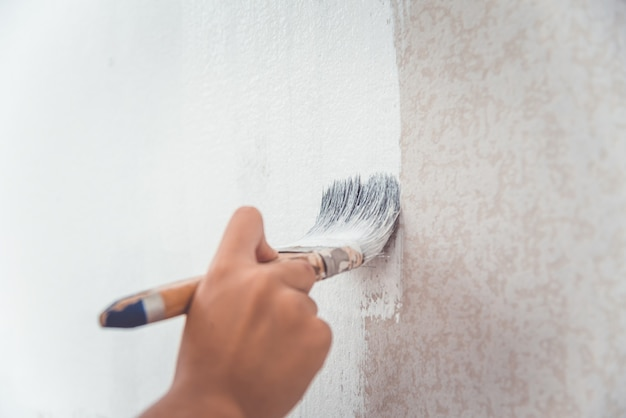 Hand hield een borstel vast om de muur te schilderen met witte verf.