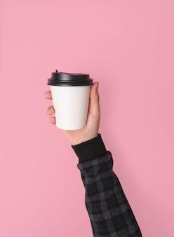 Hand holdinf koffiedocument kop. mockup voor creatief ontwerp branding geen roze achtergrond.