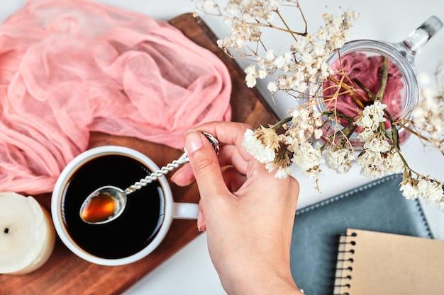 Hand holdong een kopje koffie op een houten bord met kaars, ponk doek en bloemen.