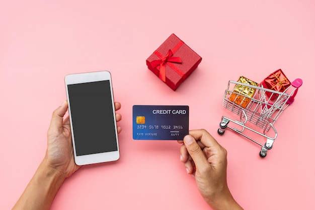 Hand holing creditcard en mobiele telefoon, winkelwagentje met geschenkdozen op roze achtergrond. winkelen, winkelen online concept, kopie ruimte, bovenaanzicht