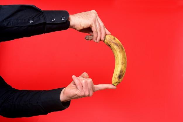 Hand honding een banaan op rode achtergrond