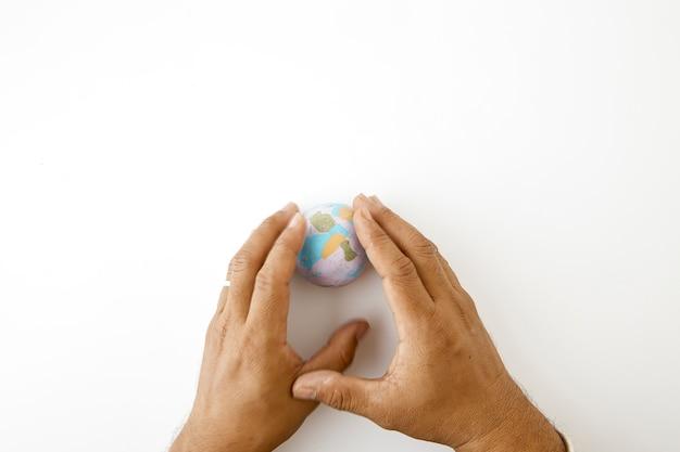Hand houd plastiline symbool van de planeet aarde bol