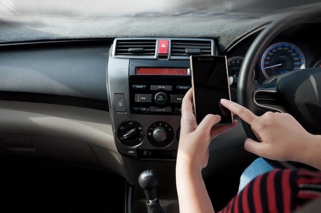 Hand houd smartphone in auto, mensen drukken richt de telefoon tijdens het rijden