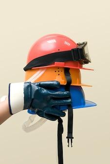 Hand houden drie gekleurde helmen