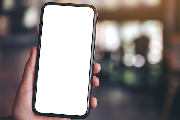 Hand houden en zwarte mobiele telefoon met leeg wit scherm in moderne café tonen