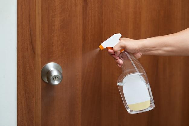 Hand houden fles alcohol sproeien desinfecterende deur.