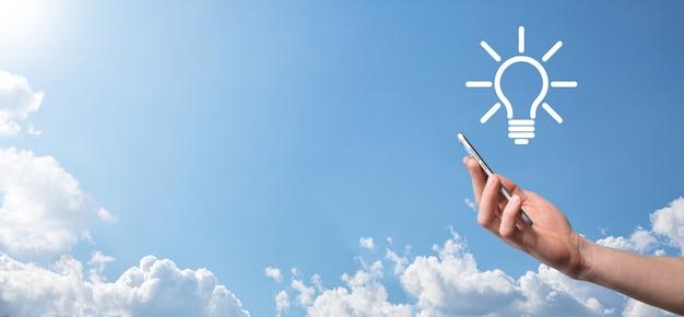 Hand houden gloeilamp. houdt een gloeiend ideepictogram in zijn hand. met een plek voor tekst. het concept van het bedrijfsidee. innovatie, brainstormen, inspiratie en oplossingsconcepten.