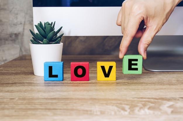 Hand houden houten kubus met tekst love op tafel