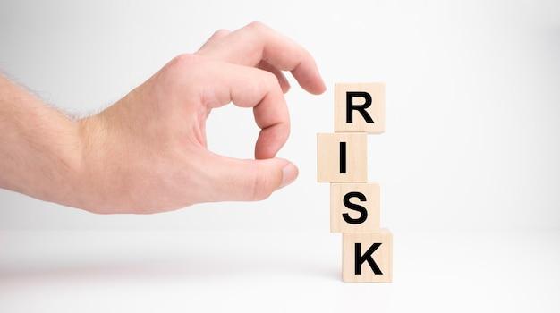 Hand houden houten kubussen met risico woord. risicobeheer concept. witte achtergrond. ruimte kopiëren.