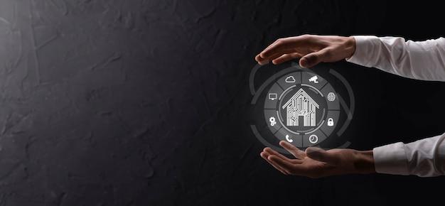 Hand houden huispictogram. smart home gecontroleerd, intelligent huis en domotica app concept. pcb-ontwerp en persoon met slimme telefoon. innovatie technologie internet netwerkconcept.