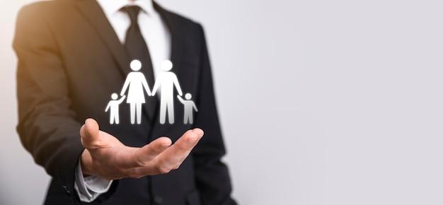 Hand houden jonge familie icoon. gezinslevensverzekering, ondersteuning en diensten, gezinsbeleid en ondersteunende gezinnen concepten. gelukkig familie concept. kopieer de ruimte. mancupped handen met papier man familie