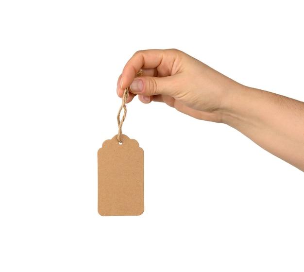Hand houden lege bruine rechthoekige bruine papieren label aan een touw geïsoleerd op een witte achtergrond, sjabloon voor prijs, korting