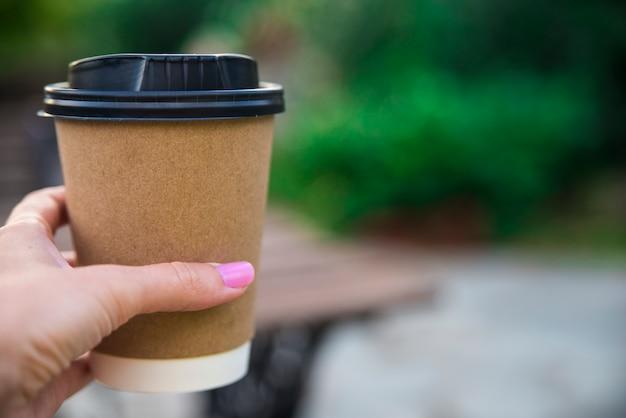 Hand houden papier kopje koffie op natuurlijke ochtend achtergrond