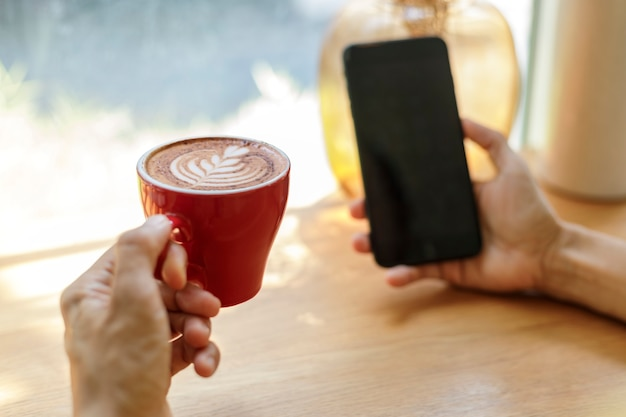 Hand houden rode kop koffie ontspannen met mobiele telefoon in coffeeshop