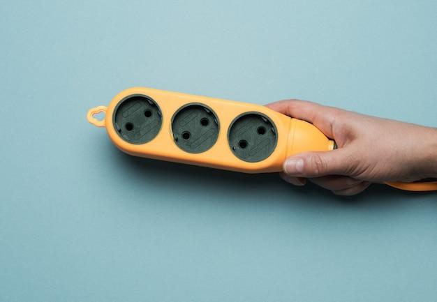 Hand houden rubberen oranje stekkerdoos met drie stopcontacten op een blauwe achtergrond, bovenaanzicht