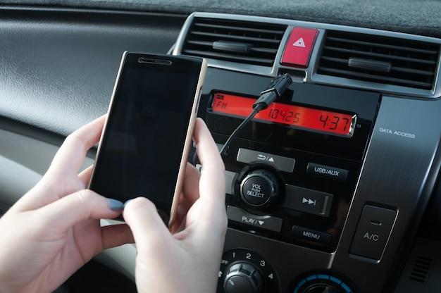 Hand houden smartphone in auto, mensen drukken op de telefoon tijdens het rijden
