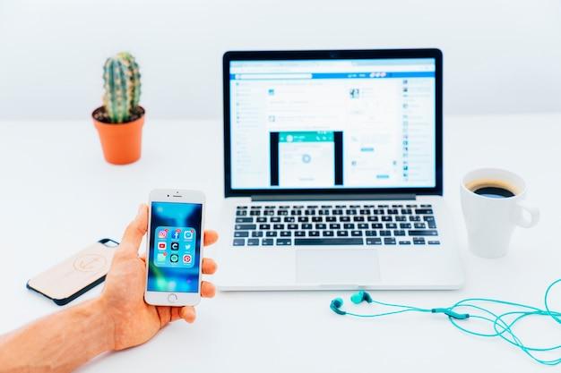 Hand houden telefoon met apps en bureau op de achtergrond