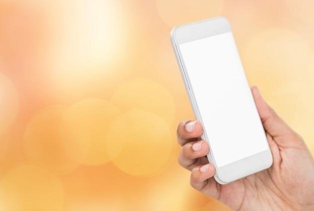 Hand houden van een smartphone op onscherpe achtergrond