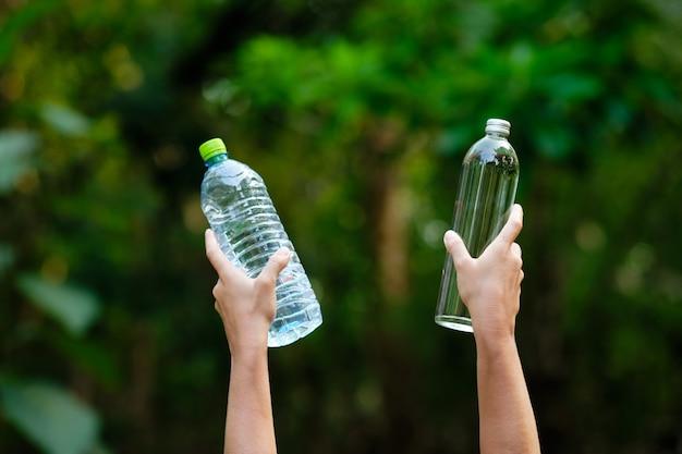 Hand houden water leeg glas en plastic fles