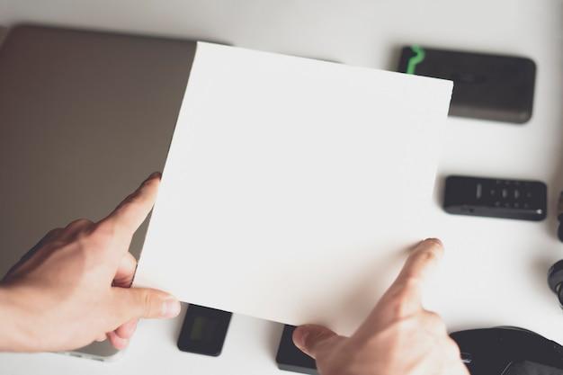 Hand houden wit vierkant in de top van moderne gadgets. kopieer ruimte b