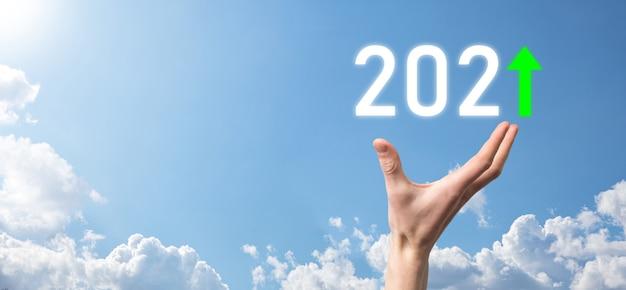 Hand houdt 2021 positief pictogram op het hemeloppervlak