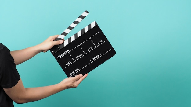 Hand houdt black clapper board of film filmklapper of leisteen op groene munt of tiffany blue achtergrond.