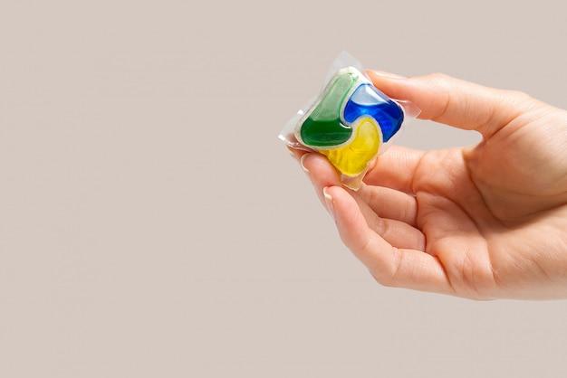 Hand houdt de afwasmachine capsule op beige achtergrond. kopieer ruimte. vrouw hand met vaatwasser wasmiddel tablet.