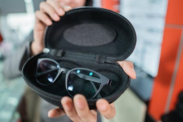 Hand houdt de bril in de lenzenvloeistofhouder terwijl de hand van de klant selecteert