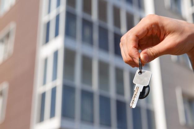 Hand houdt de sleutels van een nieuw appartement van het huis vast. housewarming en constructie