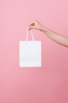 Hand houdt de tas onder het logo op een roze geïsoleerde ruimte