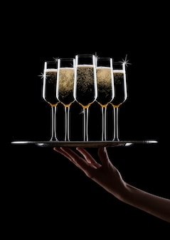 Hand houdt dienblad met gele champagneglazen