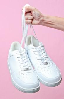 Hand houdt door schoenveters hipster witte sneakers