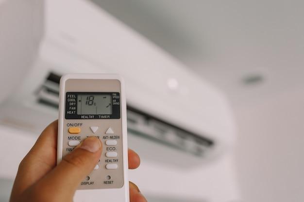 Hand houdt een afstandsbediening van airconditioner vast