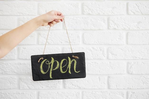 Hand houdt een bordje zeggen open op café of restaurant hang op deur bij ingang. na quarantaine. bedrijfsopening