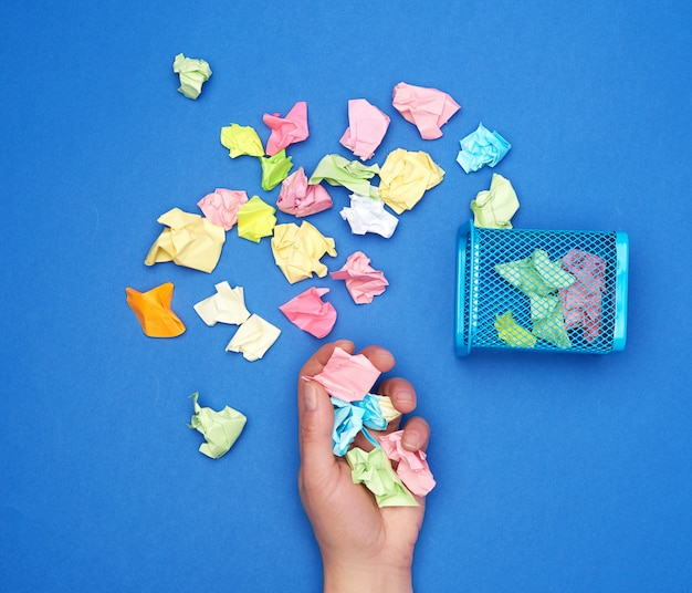 Hand houdt een bos van verfrommeld multi-gekleurde stukjes papier